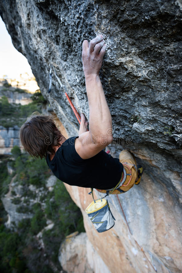 Rock climber ascending a challenging cliff. Extreme sport climbing. Freedom, risk, challenge, success. Sport and active royalty free stock image