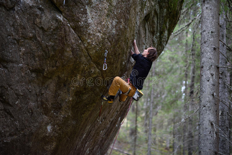 Rock climber ascending a challenging cliff. Extreme sport climbing. Freedom, risk, challenge, success. stock photo