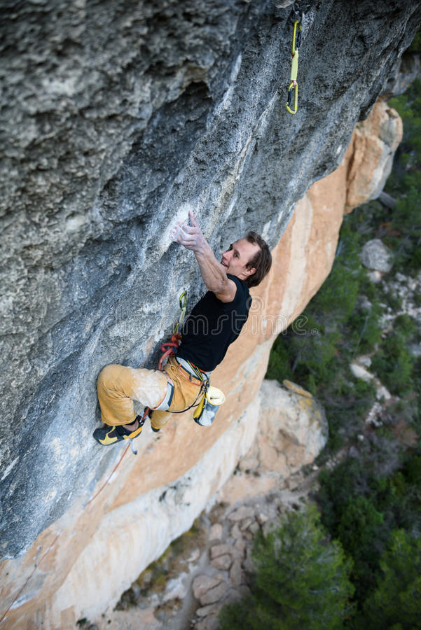 Rock climber ascending a challenging cliff. Extreme sport climbing. Freedom, risk, challenge, success. Sport and active life stock images