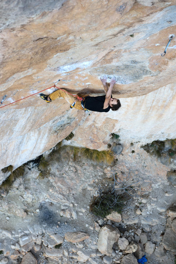 Rock climber ascending a challenging cliff. Extreme sport climbing. Freedom, risk, challenge, success. Sport and active life stock photo