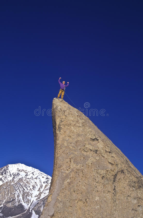 Rock climber celebrates on the summit. stock photo