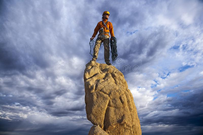 Rock climber celebrates on the summit stock photography