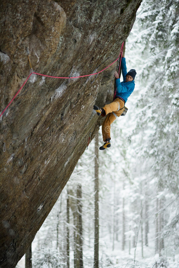 Rock climber on a challenging ascent. Extreme climbing. Unique winter sports. Scandinavian nature. stock images