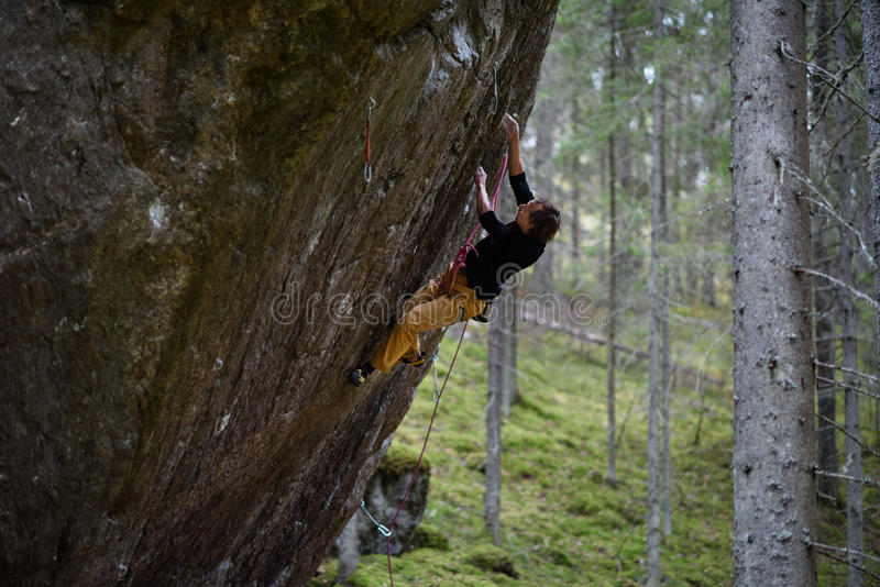 Rock climber on a challenging ascent. Extreme climbing. Unique winter sports. Scandinavian nature. stock image
