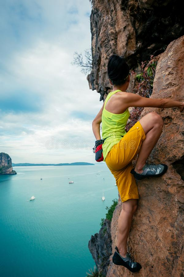 Rock climber climbing on seaside steep cliff. Female rock climber climbing on seaside steep cliff royalty free stock photography