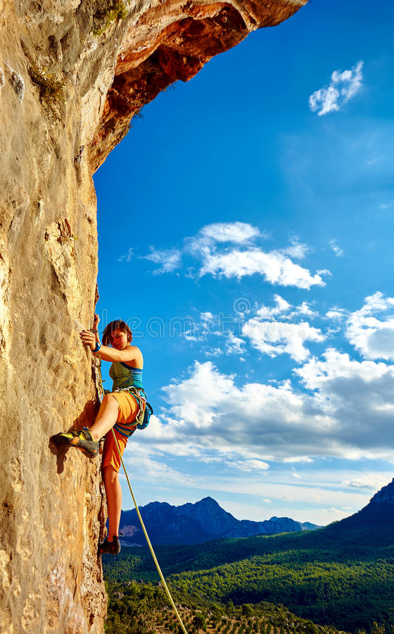 Rock climber climbing up a cliff stock photo