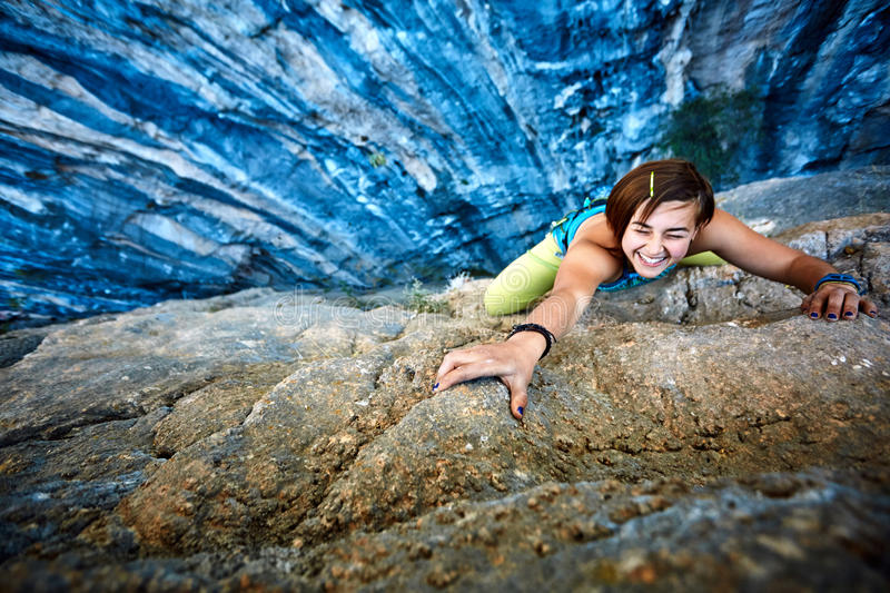 Rock climber climbing up a cliff royalty free stock image