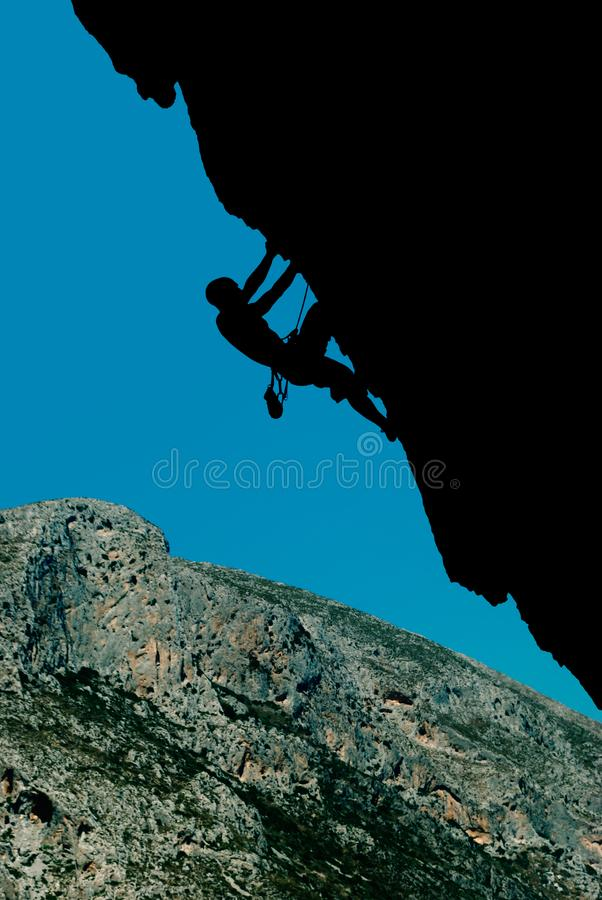 Silhouette of a climber on an overhanging rock against the backdrop of a rocky island stock image