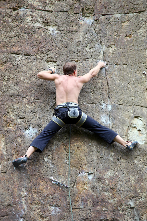 Rock climber clinging to the rock. The leader of the roped party royalty free stock images