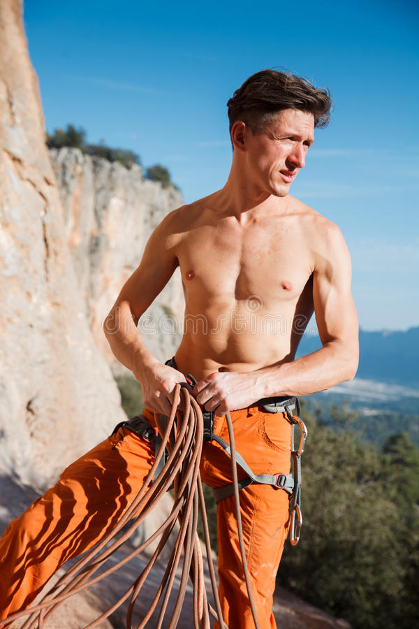 Rock climber collecting belay rope over the mountains royalty free stock photos