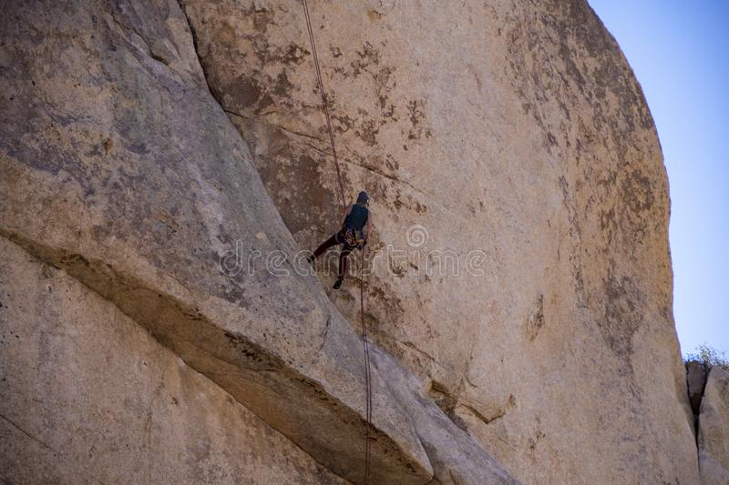 Rock Climber scaling a huge Boulder of Joshua Tree National Monument royalty free stock photos
