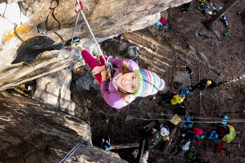 Rock-climber girl crying in pain hanging on a rope with a sad face when climbing on a rock royalty free stock photography
