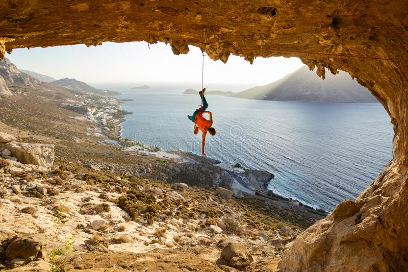 Rock climber hanging on rope after falling of cliff, climbing in cave royalty free stock images