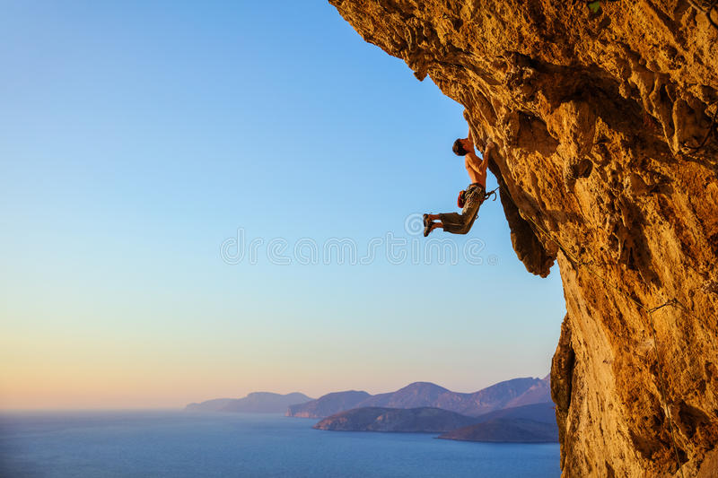 Rock climber jumping on handholds royalty free stock image