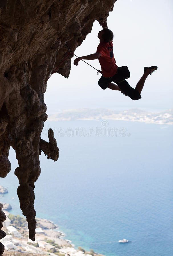 Rock climber jumping on next handhold stock images