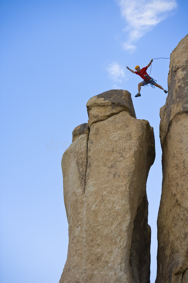 Rock Climber Jumping For The Summit. Stock Photos
