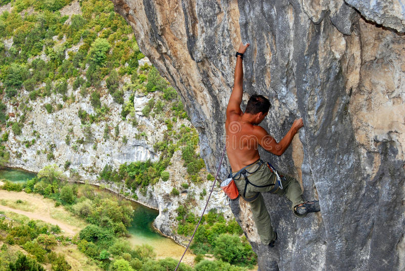 Rock climber moving up the rock stock image