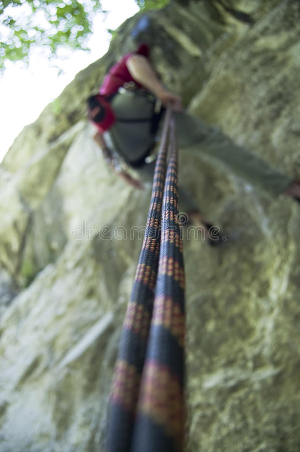 Rock climber rappelling stock image