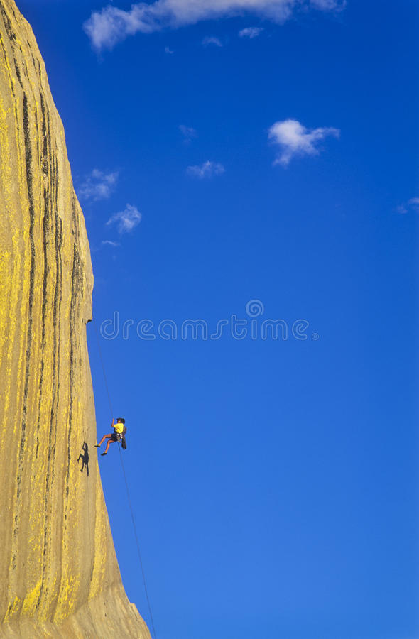 Rock climber rappells. stock photos