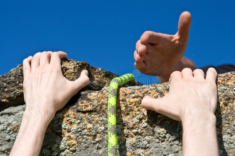Rock climber reaching for helping-hand partner. royalty free stock image