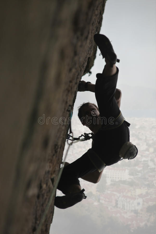 Rock climber ready for a jump. Rock climber on the rockface preparing for a jump stock photo