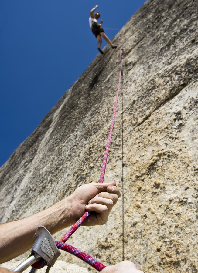 Rock climber and safety rope. royalty free stock images