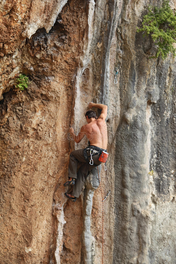 Rock climber struggling on his way up to the top. Male rock climber struggling on his way up to the top stock photo