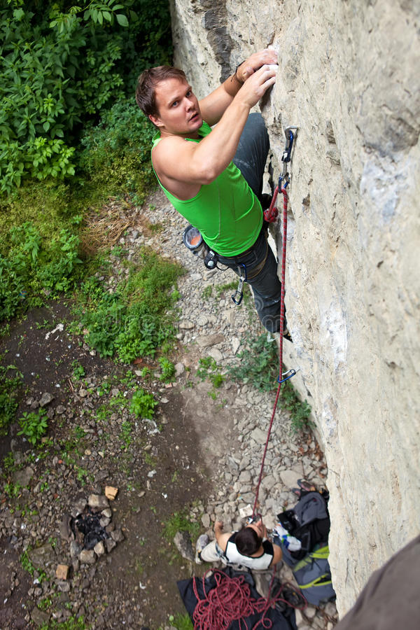 Rock climber struggling to make next movement stock photo
