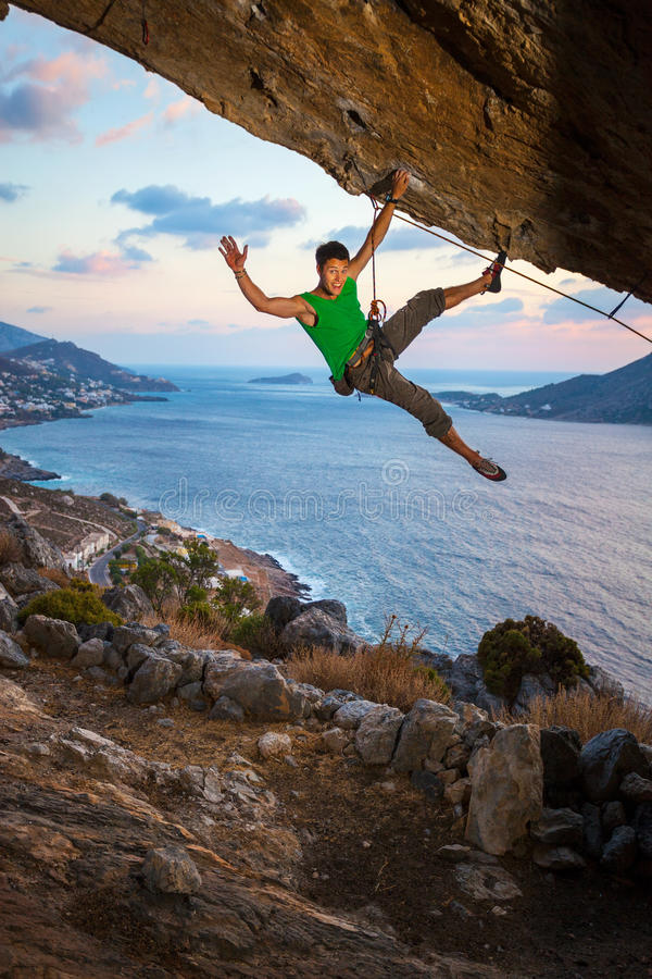 Rock climber waving his hand while climbing. Cheerful rock climber waving his hand while climbing at sunset stock photo