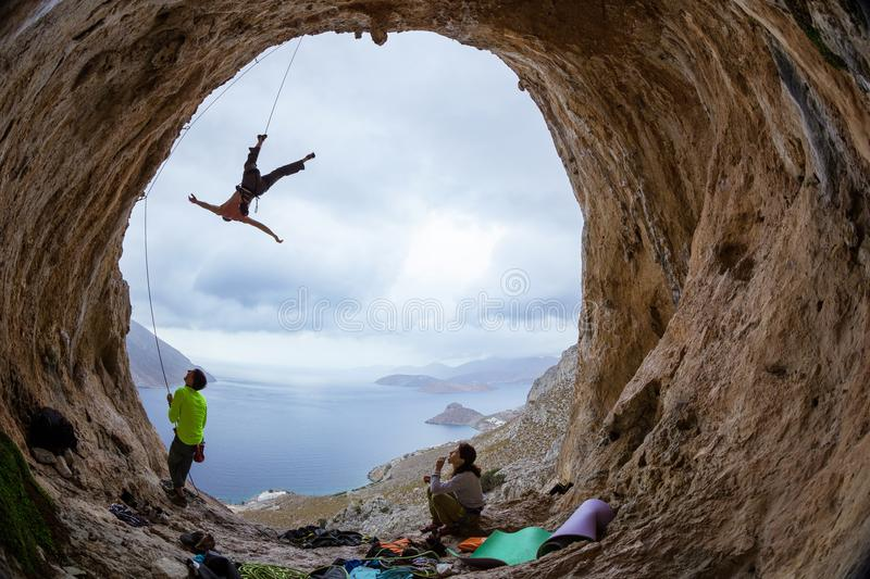 Rock climbers in cave: leading climber swinging on rope after falling of cliff. Belayer and female climber watching him royalty free stock photography
