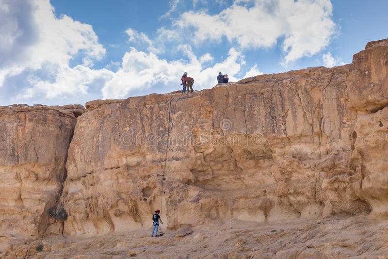 Rock climbers on the cliff of the crater Makhtesh Ramon in Israel`s Negev desert. Sports outdoor activities stock photo