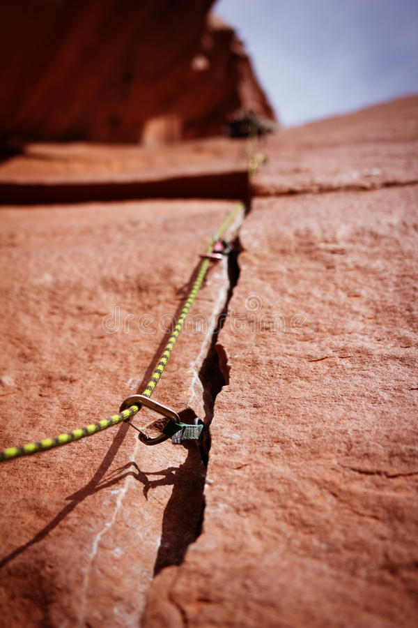 Rock climbing gear in crack royalty free stock photography