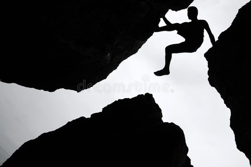 Rock climbing,Man climb between three rock on the cliff. royalty free stock photos