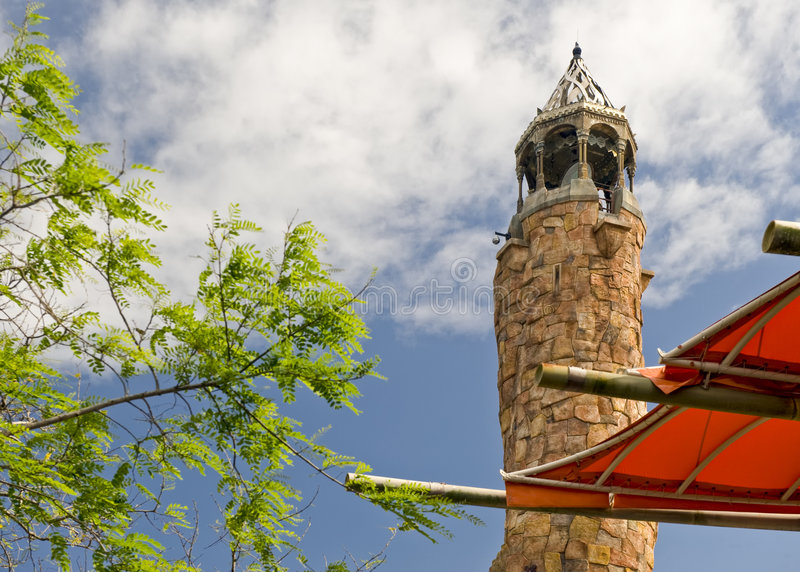 Rock climbing tower. A view past a tent canopy or awning and tree branches to a tall rock climbing tower nearby royalty free stock image