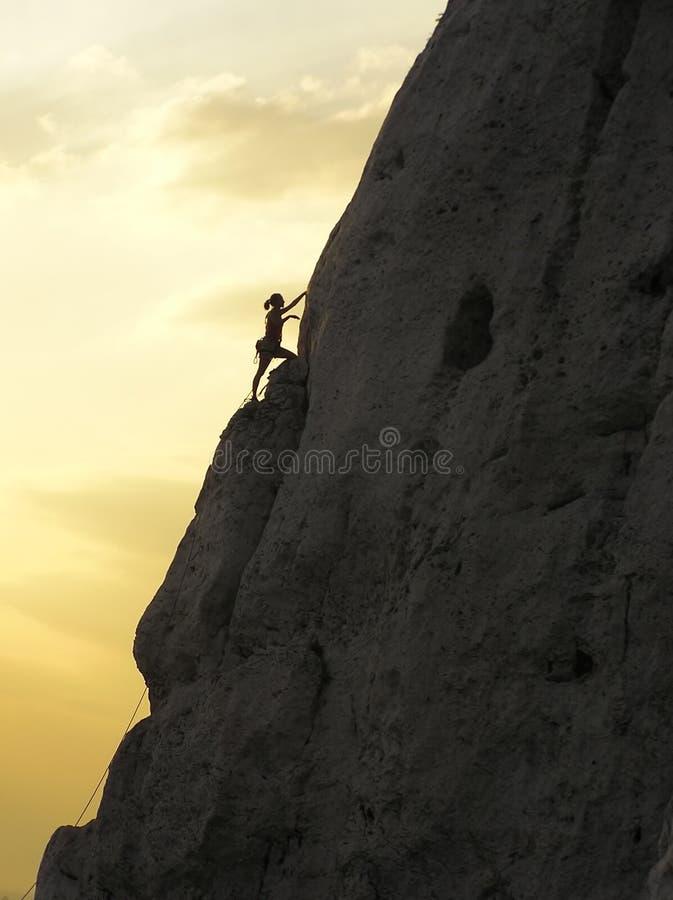 Rock Climbing Woman. Silhouette of a woman rock-climbing at sunset stock images