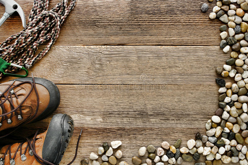 Rock Climbing Wood Background with Rope and Shoes. Rock climbing background with safety rope and traditional mountain hiking shoes on old wood board plank with royalty free stock images