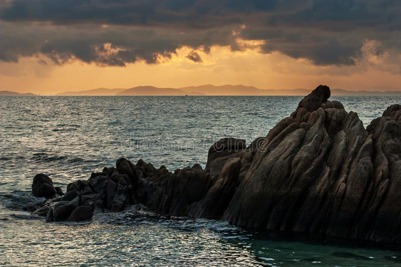 Rock on coastline on foreground during sunset with mountain range in orange sunlight as background royalty free stock photo
