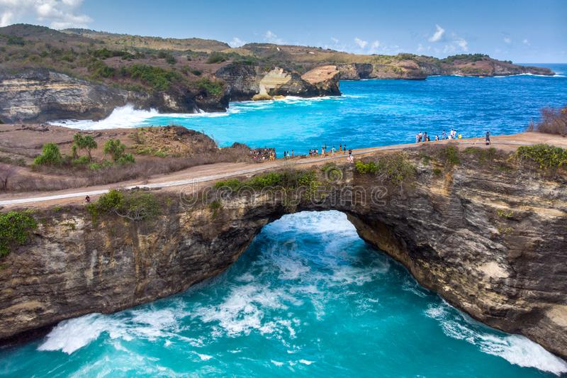 Rock coastline. Stone arch over the sea. Broken beach, Nusa Penida royalty free stock photo