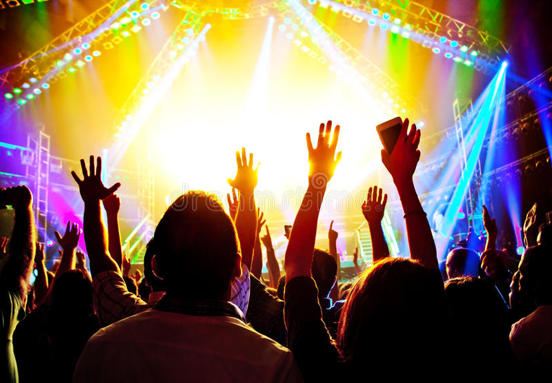 Rock concert. Happy people silhouettes, raise up hands, disco party with large group of dancing man, bright colorful stage lights, active lifestyle, music stock photos