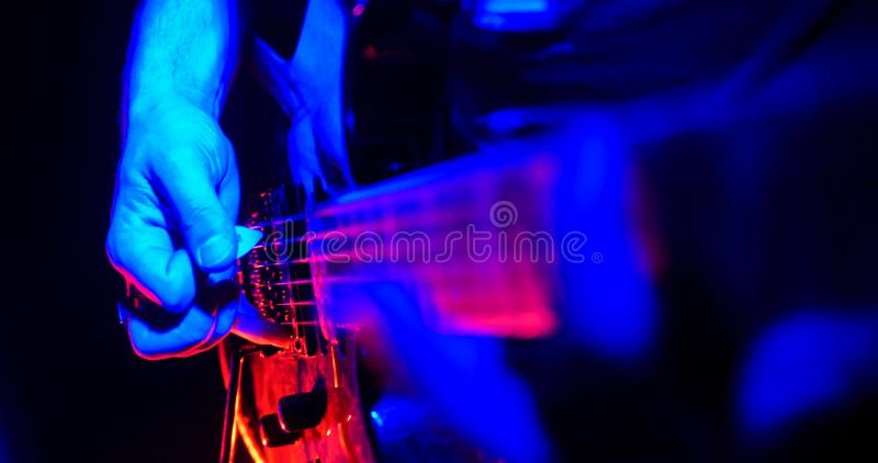 Rock concert. Guitarist plays the guitar. The guitar illuminated with bright neon lights. Hand close up royalty free stock photos