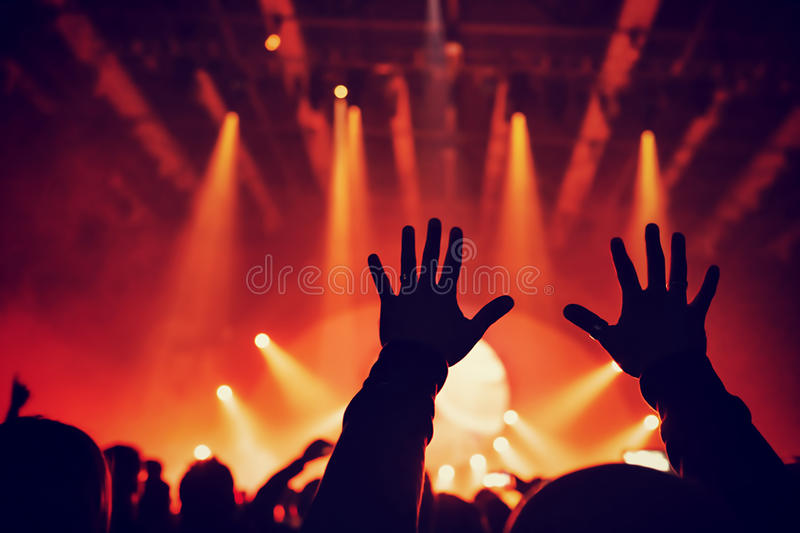 Rock concert. Silhouette of raised up man's hands over bright red lights, people having fun in night club, dancing and listening music stock photos