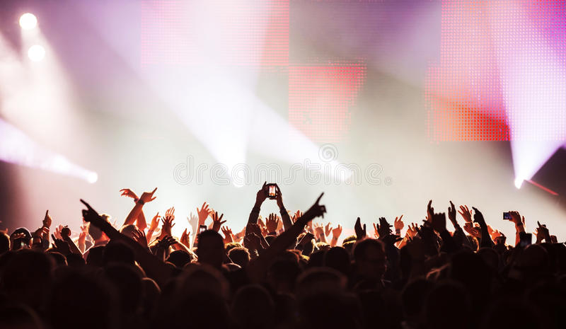 Rock concert. Silhouettes of concert crowd in front of bright stage lights stock photos