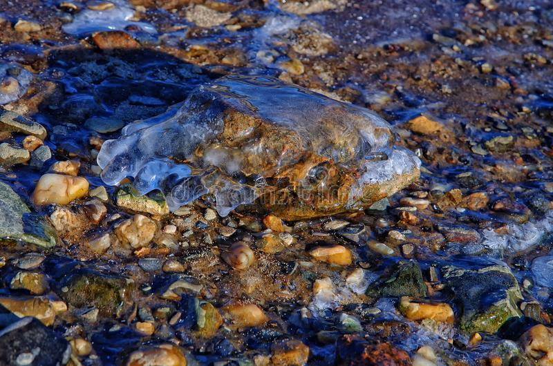 Rock covered with ice on the shore of a freezing river stock photo