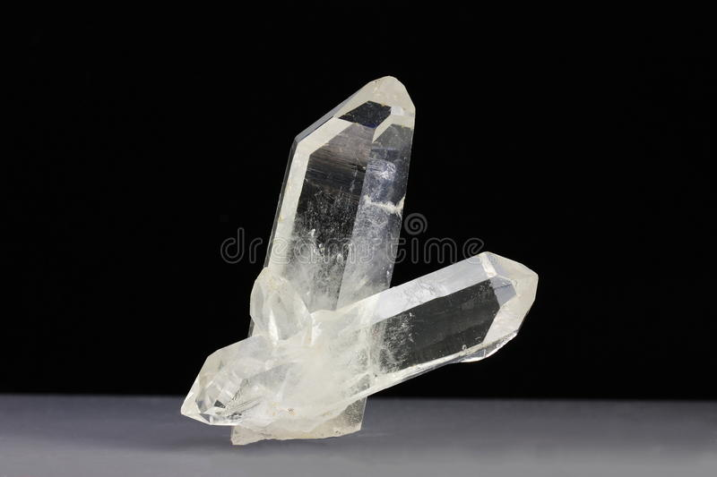 Rock crystal quartz. Two clear quartz crystals, variety rock crystal, one of which is double terminated. Quartz is a silicate mineral which is an electrical royalty free stock image