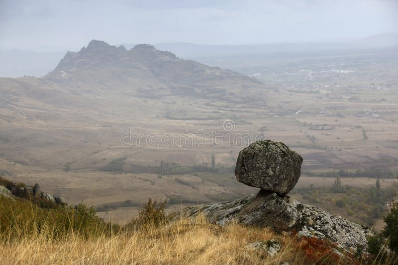 Rock defies laws of gravity - Prilep region, Macedonia. Rock that defies the laws of gravity. Out of focus background with Markovi Kuli on the top of the hill stock images