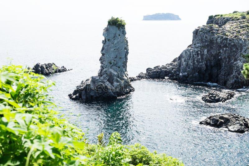 Rock formation Oedolgae in the illuminated ocean at Seogwipo, Jeju Island, Korea stock image
