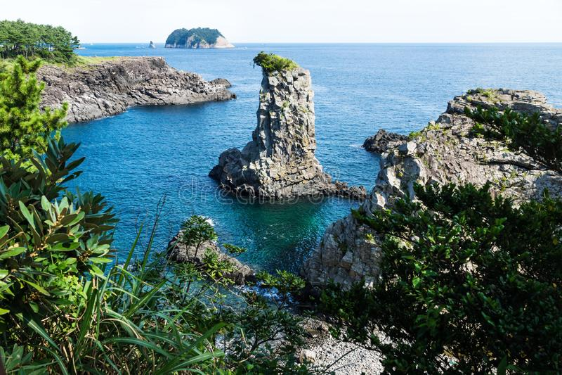 Rock formation Oedolgae surrounded by cliffs and forest in the ocean at Seogwipo, Jeju Island, Korea stock images