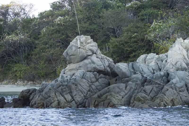 Rock formation over the sea in the shape of a lion, bahias de huatulco, Oaxaca Mexico. Coast, cliff, blue, waves, water, island, green, vacation, travel royalty free stock photo