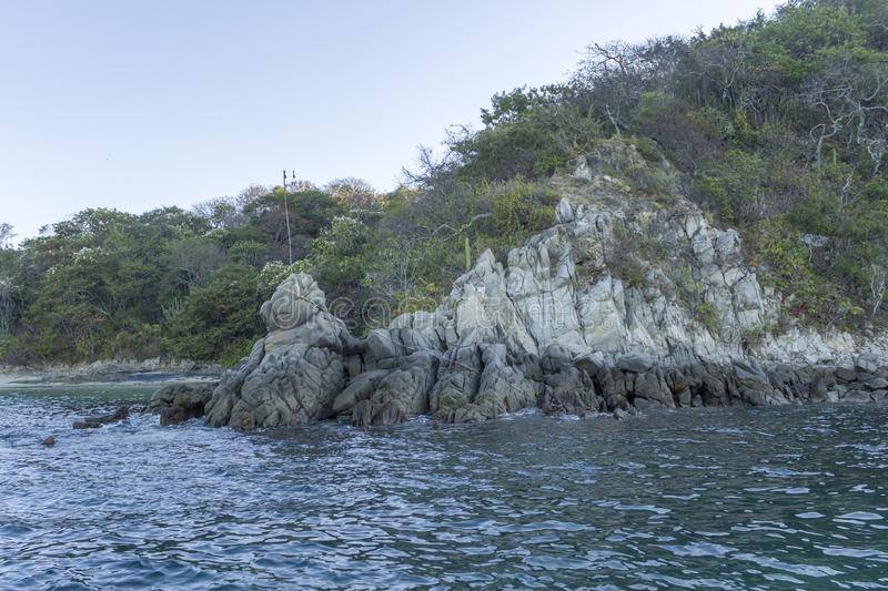 Rock formation over the sea in the shape of a lion, Huatulco bays, Oaxaca Mexico. Coast, cliff, blue, waves, water, island, green, vacation, travel, diving stock image