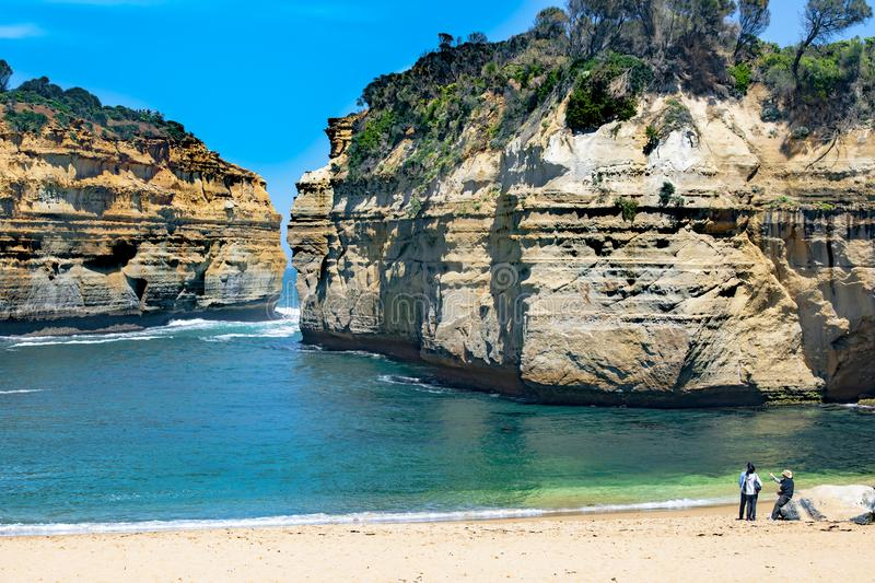 Couple in wonder of rock formations in bay Twelve Apostles, Australia, morning light at rock formation stock images